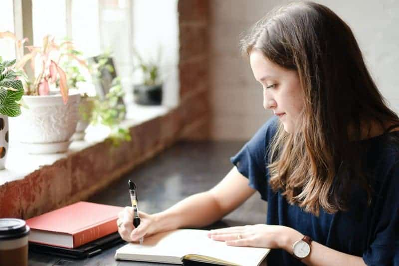 girl in a hostel wring in her travel journals