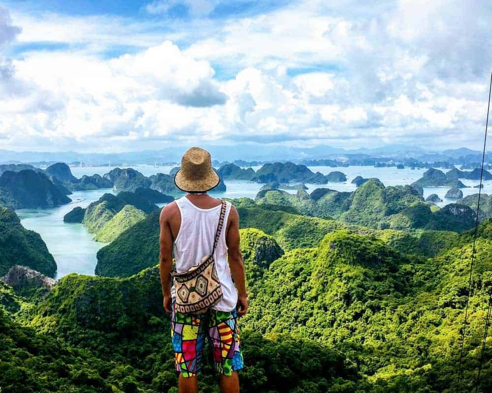 man standing on a hill looking at halong bay