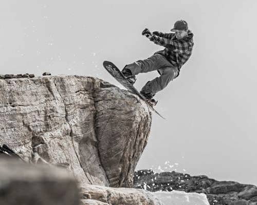 Man On a Rock with snowboard - Norway Travel Guide