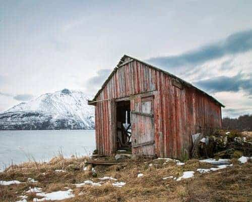 Red Barn on the lake with snow covered mountains behind