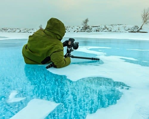 photographer takes pictures bubbles of methane gas frozen into clear ice lake Baikal, Russia.