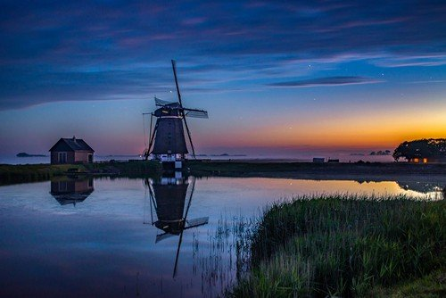 Sunset on the coast of Holland with windmills in the distance - netherlands regional travel guide
