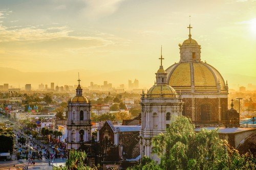 Basilica of Guadalupe with Mexico city skyline at sunset, Mexico - Ultimate Mexico Travel Guide