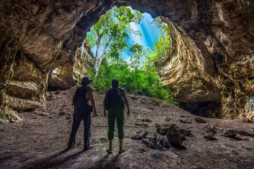 Two male explorers standing at bottom of circular cave opening in jungle of Chiapas, Mexico - Ultimate Mexico Travel Guide