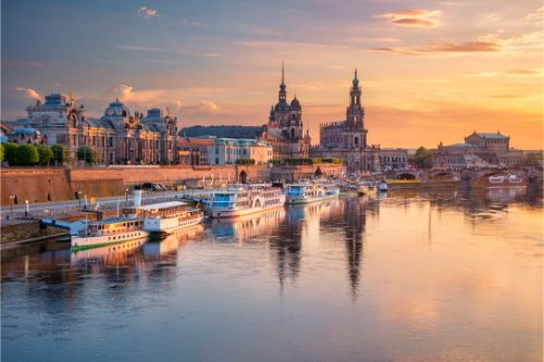 Cityscape image of Dresden, Germany with reflection of the city in the Elbe river, during sunset.