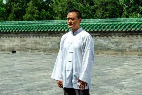 Chinese Many In Traditional Clothing Practicing Tai Chi Exercises