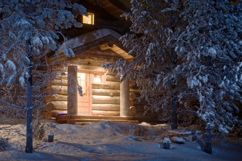 Cozy wooden cottage in dark winter forest - ultimate finland travel guide