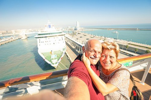 Senior happy couple taking selfie on ship at Barcelona harbour - benefits of travel for senior citizens