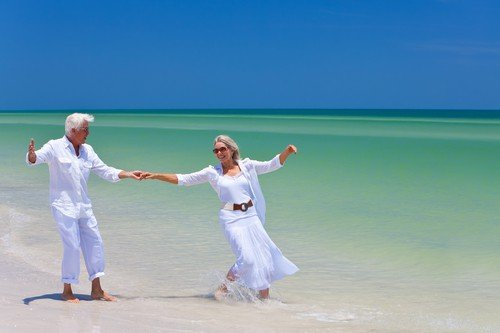 Happy Senior Couple Dancing Holding Hands on A Tropical Beach - benefits of travel for senior citizens