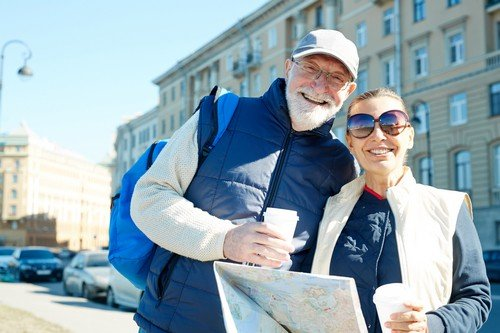 Senior female in sunglasses and her husband with backpack in urban environment