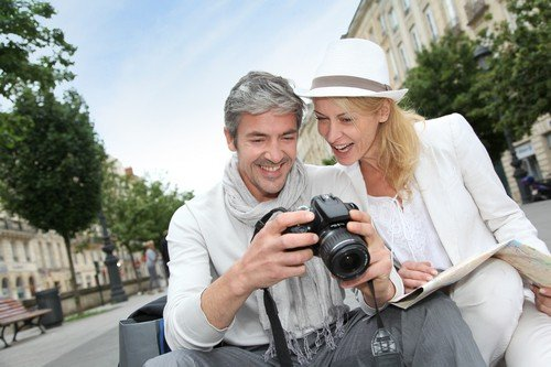 Happy tourists looking at pictures on camera screen