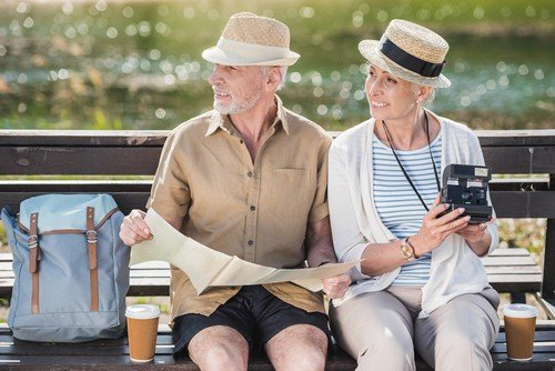 Happy senior couple of travelers sitting together on bench and holding map and instant camera