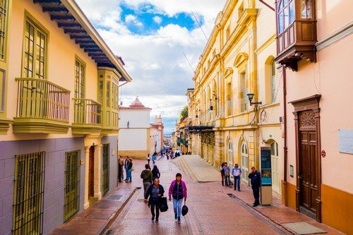 Typical charming street in old part of Bogota with people walking on red stoned pavements sorrounded by spanish colonial architecture and yellow buildings - ultimate colombia travel guide