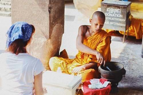 Young monk offering written blessings to a tourist.