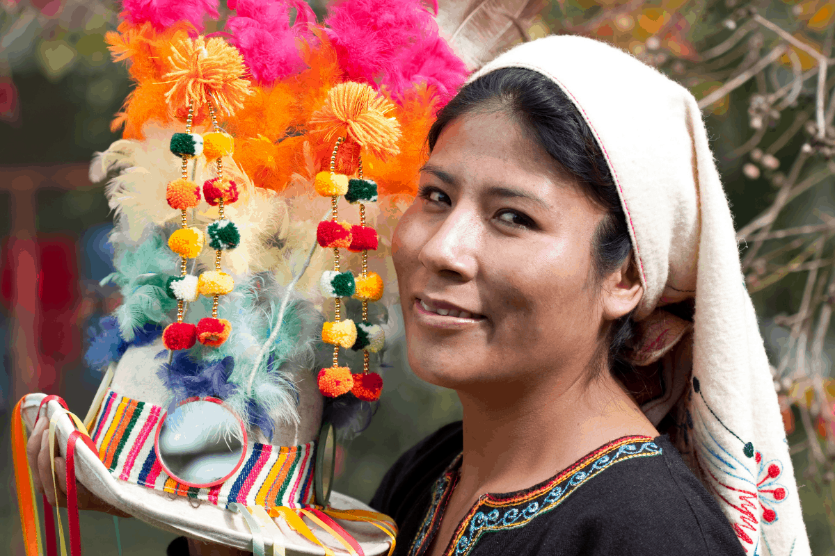 Bolivian woman holding a hat with feathers