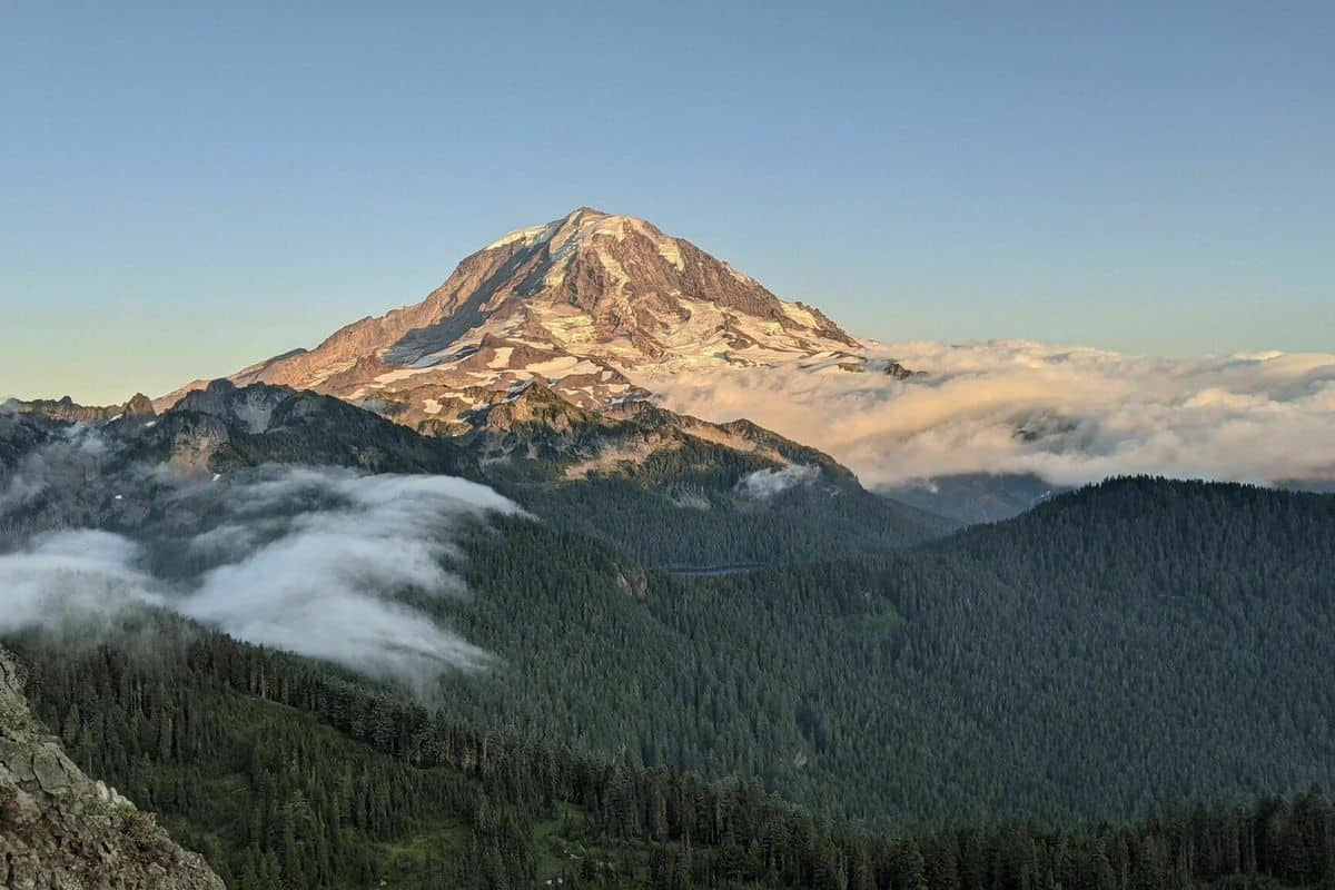 Aerial View of Mount Rainier at sunrise surrounded by clouds - Boondockers Welcome