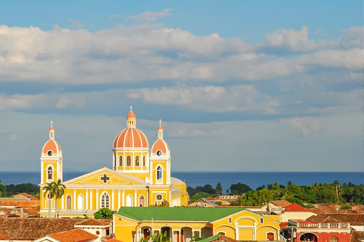 The skyline of Granada, Nicaragua, with its yellow cathedral, rooftops in Spanish-colonial-style architecture and Lake Nicaragua in the background.